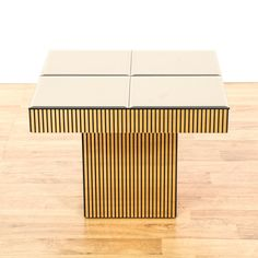 This square end table is featured in a solid wood with a shiny gold finish. This contemporary style side table has a 4 tile mirrored top, vertical line design, and square base. Perfect next to the couch! #contemporary #tables #endtable #sandiegovintage #vintagefurniture