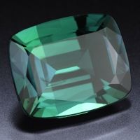 alexandrite, the color-change gem. Outside in daylight, it is a cool bluish mossy green. Inside in lamplight, it is a red gem, with a warm raspberry tone.
