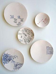 serie de platos con motivos finos pintados encima: lista de la compra, recados, números...