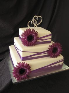 """Purple ribboned cake for Wedding Planning Expo - Three square tiers - 6"""", 9"""" and 12"""" covered in white fondant and decorated with various widths of purple ribbon wrapped around the cake, plus three large purple gerberas. Topper is some Wilton thing I had on hand. Thanks for looking."""