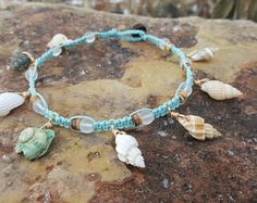 Super sweet and lovely, this anklet is sure to become your newest favorite piece of jewelry!  Tied with natural hemp this is beachy and fun... Ive placed the 3 cowrie shells on the side of the anklet so they will sit to be seen. Surrounding the shells Ive placed gorgeous small green jade beads and blue Aventurine gemstones. Just gorgeous. It measures 9.5 inches around and has a nice wood disk bead and loop closure. Secure and fashionable!  If you have any questions please dont hesitate to…