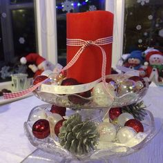My table centre piece! 2 glass cake stands, baubles, ribbon etc, LED candle, and a simple ready made decoation