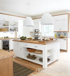 Sleek dome pendant lights play with scale and bring a contemporary feel to this cottage kitchen. Butcherblock countertops add warmth to the all-white space. | Photographer: Virginia Macdonald | Designer: Montana Burnett