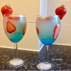 HOLY WATER 1 oz. (30ml) Vodka 1 oz. (30ml) Rum ½ oz. (15ml) Blue Curacao ½ oz. (15ml) Peach Schnapps 4 oz. (120ml) Lemonade Splash Pineapple Juice Sliced strawberries