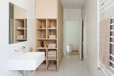 This home in Melbourne by design duo Kathryn Robson and Susie Cohen has deep nook shelves at one end of the wardrobe, which gives the bathroom a warm, natural and organic feel.