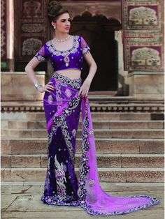 This nett saree in blue is a perfect one for weddings and sangeets. The saree is embellished with heavy stone work and designer work all over the saree, while the pallu has a contrasting color with heavy motifs on it. The blouse has heavy designer all over it. So look the most glamorous and gorgeous and stun everyone with your look. (Slight variation in color is possible)