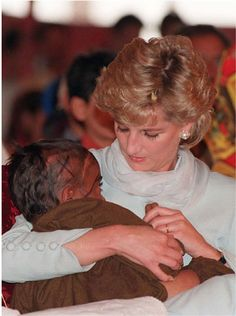 Diana is moved to tears as she cradles a sick child in her arms during one of many visits to Imran Khan's cancer hospital in Lahore Lahore, Pakistan