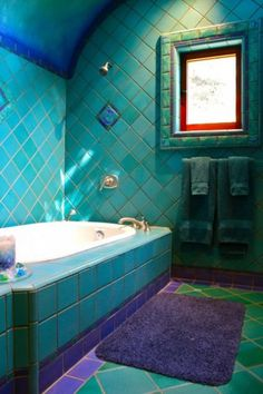 The striking bathroom is covered floor to ceiling with saturated blue tiles