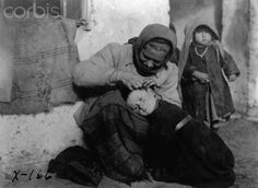 An old woman picks lice or bugs from the scalp of a young boy. Their family are refugees from the fighting of World War I. Serbia, December 1918. | Location: Leskovac, Serbia.