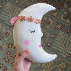 "This sweet and sleepy moon is handcrafted from vanilla hued velveteen and crowned in a ring of shimmering stars. She has carefully embroidered eyelashes, rosy blushed cheeks, a heart-shaped kisser and loves to dream the day away in a pretty pile of pillows8"" x 11"""