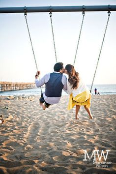 bride and groom-to-be on swings on the beach. save the date photo idea