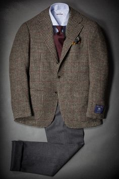 Brown tweed jacket, light blue shirt, dark red tie, dark grey pants