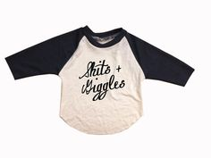 Super soft and stretchy hand made baby raglan with dark navy sleeves and cream body with funny hand painted Shits + Giggles in cursive on front.