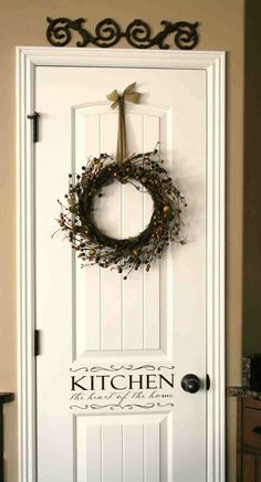 Love everything about this! Pretty wreath with a pretty satin ribbon, stenciled writing on the door, and the wrought iron flourish above the door! MV