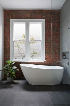 In this updated bathroom with large dark grey tiles and a white freestanding bathtub, the heritage parts of the house were retained, like the brick wall that's been left on display instead of covered up.