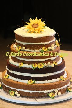 Naked wedding cake.  This naked sunflower wedding cake was designed by C. Bird's Coordination & Design, an OKC home bakery and coordination service. The layers are chocolate chip and brownie with cream cheese frosting in between. A gum paste sunflower sits on top and buttercream wild sunflowers with twigs and berries accent the sides of the cake. Email at 2cbird@cox.net