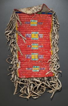 A SIOUX QUILLED AND BEADED HIDE POUCH,     the front decorated with a column of cross motifs stitched in yellow, green, purple and red-dyed porcupine quills, trimmed with a band of green, blue, and red glass seed beads and short hide fringe