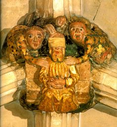 Carved roof boss from the nave vault of Norwich Cathedral, representing the buffeting of Christ. The blindfolded figure of Christ is seated on a bench, being held down by two torturers, who each have a hand on his shoulders. With the fingers of his free hand, the torturer on the left clutches Christ's head. The torturer on the right holds up his fist, about to punch Christ on the head. This torturer is sticking out his tongue in mockery.