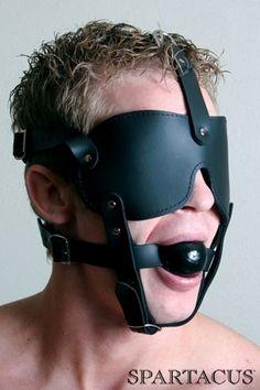 Masque harnais en cuir avec baillon boule. Il aveugle et réduit le soumis au silence