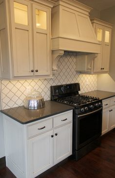 "Flooring: Paramount Mountain Heritage Oak 5"" in brown; Backsplash: Highland Park Arabesque, Antique White with iron grout"