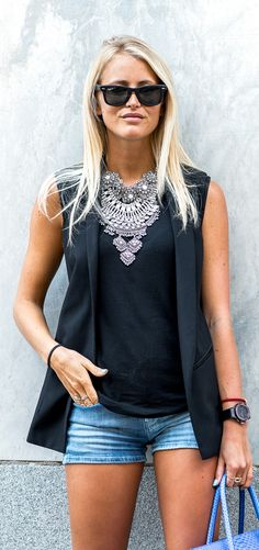 Janni Deler is wearing a black top H&M, black vest from Zara, and denim shorts from MIH