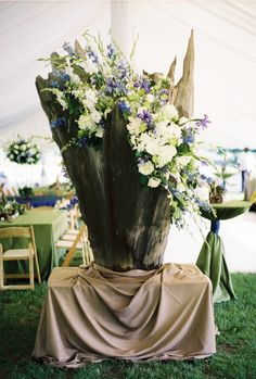 amazing white, blue and green florals in a huge tree trunk under a tent - wedding recepetion - Kim Box Photography (Josh Moates); Southern Wedding Designs (florist)