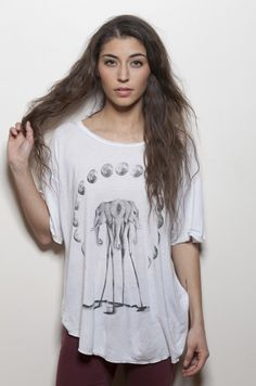 """A tribe of wandering elephants moving silently under crescent moons.  Paying homage to Dali's infamous creatures.   Original hand-drawn sketch by Neoclassics.  Printed on our """"Boyfriend T"""", soft silicon washed white fabric custom cut/sewn/dyed in Los Angeles. Drop shoulders, raw edge finish and..."""