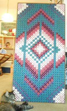Large scale cross-stitch done on pegboard with yarn. My kitty is posing for size comparison.