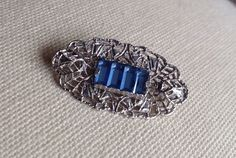 Delicate filigree vintage brooch set with blue bevelled glass. A lovely item made from a silver tone metal in Art Deco style and measuring approx 3.5 x 2 cm.