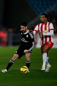 Francisco Roman Alarcon alias Isco (L) of Real Madrid CF competes for the ball with Michel Macedo Rocha (R) of Almeria UD during the La Liga match between UD Almeria and Real Madrid CF at Juegos del Mediterraneo stadium on December 12, 2014 in Almeria, Spain.