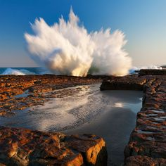 landscape photo of a wave crashing into the air on South Africa's wild coast
