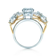 Set in platinum with 18k gold accents, a round brilliant Tiffany diamond is framed by magnificent stones fashioned to resemble bees, a traditional symbol of royalty.
