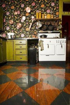 Nesta #cozinha, nada é neutro! Losangos foram pintados no chão de madeira, as paredes são revestidas com um tecido floral e armários verdes completam a #decoração campestre. Gostou?