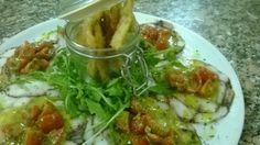 Carpaccio di polipo con rucola, pomodorini e salsina al pesto. Octopus carpaccio with arugula, cherry tomatoes and pesto sauce.