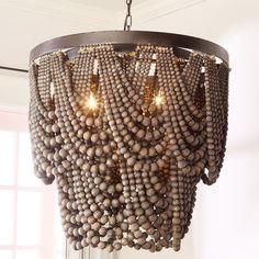 Check out Bohemia Draped Bead Chandelier from Shades of Light This large chandelier has a Boho chic flair with its multiple draping beads, in shades of gray and black, staggered around a dark metal frame and cascading down to form two scalloped rows. Wood Bead Chandelier, Black Chandelier, Chandelier Shades, Chandelier Ideas, Dining Room Light Fixtures, Dining Room Lighting, Large Chandeliers, Custom Drapes, Room Lights