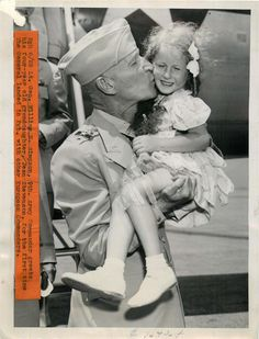 1945- Lt. Gen. William Simpson, 9th Army commander, shown kissing his granddaughter after arrival in Pittsburgh from war in Europe.