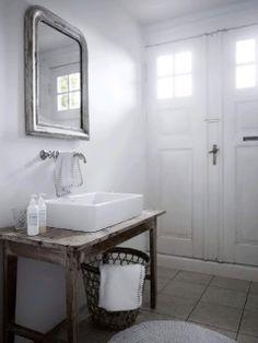 Lovely coastal bathroom design with cafe au lait walls paint color, silver leaf beveled bathroom mirror, brushed nickel bridge wall-mount bathroom faucet, reclaimed wood bathroom vanity shelf, pocket doors and white overmount sink. Wood Bathroom, White Bathroom, Bathroom Interior, Modern Bathroom, Bathroom Basin, Bathroom Vanities, Bad Inspiration, Bathroom Inspiration, Dream Bathrooms