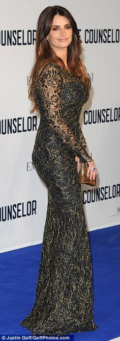 Vamping it up: Clinging to every curve, the breathtaking dress featured an unusual black and gold lace overlay with elongated sleeves, provi...