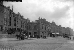 Perth Road, Dundee - This photograph shows the point where Perth Road meets Hawkhill, known locally as The Sinderins. Slightly to the east and left of the image, Blackness Avenue leads northwards towards Balgay Park.  The block of three-storey buildings is known as Manor Place. None of the businesses is easily identified. The West End Drapery Warehouse may have been Jessie Croll and John Pringle, listed as Nos. 217 and 219 Perth Road for over ten years.