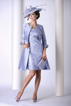 ENFI 2701-2704 (Mireia) In a soft lilac, this lace dress and coat is stunning. The dress has a lace overlay and a detailed band which sits under the bustline. The coat has a rounded neckline and is button fronted. The Read More...