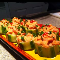 Homemade spicy tuna cucumber cups. Be sure to use sushi grade tuna with rooster sauce and plain Greek yogurt. Top with green onions
