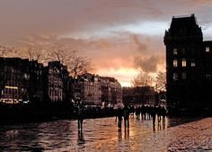 Rita Crane Photography:  Paris / Ile de la Cite / sunset / silhouette / sky / umbrellas / rain / people / architecture  / Rainy Evening at Place du Parvis Notre Dame, Paris