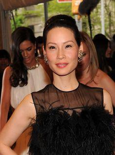 Lucy Liu Dangling Gemstone Earrings - Lucy Liu paired her elegant ballerina bun with chunky gemstone earrings.