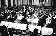 Karl Eliasberg dirige a la Filarmónica de Leningrado el 9 de agosto de 1942, interpretando la 7ª Sinfonía que Shostakovich dedicó a su ciudad asediada por las tropas nazis. Tras un año de bombardeos, hambre y muerte solo 15 miembros de la orquesta quedaban con vida. Se tuvieron que buscar músicos entre la famélica población que apenas podían tocar sus instrumentos. Finalmente, el mítico concierto tuvo lugar, con altavoces por toda la ciudad que resonaron hasta llegar a los propios alemanes.