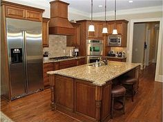 Love that cinnamon maple kitchen cabinet color, and the huuuuuge island for prep or buffet space
