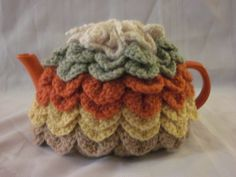 I finally figured out how to make a scalloped tea cozy!  This is my finished project.  This tea cozy is very easy once you figure out the pattern. And works up quickly.  It keeps the pot warm for a fairly long time.  If you have trouble with this pattern, email me!  (I used up leftover yarn for this)