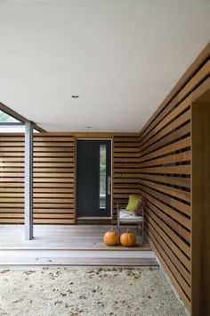 The slatted cedar siding continues to wrap around the front door leading visitors to a new covered entry deck. Through the vertical slot in the front door you get a hint of the wall of glass beyond in the foyer.