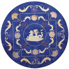 A SCAGLIOLA TABLE TOP  20TH CENTURY  The circular top with a faux lapis ground decorated with a central medallion of a putto riding a seahorse surrounded by a ring of mermaids, coral and shells, the outer border with pearls, coral and fish