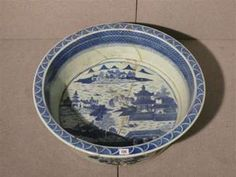 A large circular 18th century Chinese foot bath decorated in a blue willow pattern.