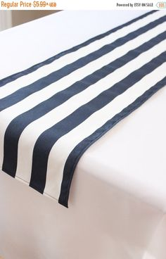 This navy blue and white striped table runner is the perfect compliment to your…